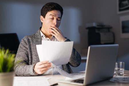 Sleepy hombre asiático trabajando horas extraordinarias