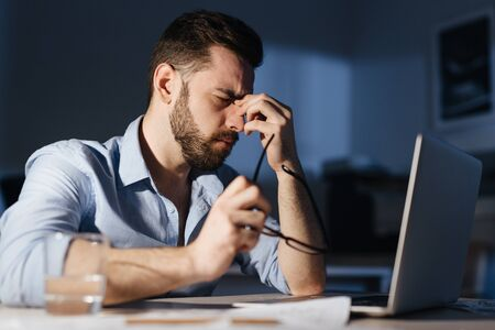 Exhausted Man Working Overtime in Dark Office Stock Photo