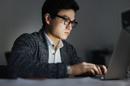 夜のラップトップで働くアジアの男