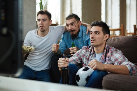 adult entertainment: Emotional Football Fans watching Match on TV Stock Photo