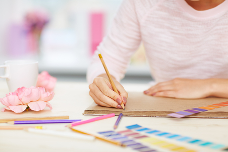 creating: Close-up shot of female hands taking notes, color swatches, pencils and flowers lying on white desk Stock Photo