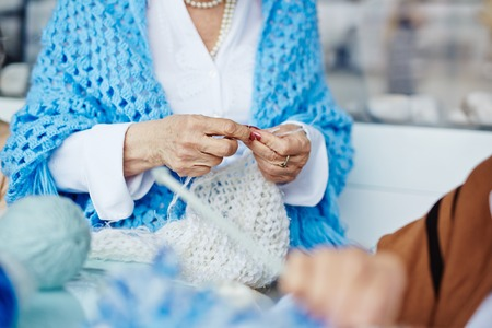 laps: Elegant-looking senior woman in white shirt and cornflower blue shawl sitting indoors with unfinished knitted scarf on laps, colorful yarns lying on table