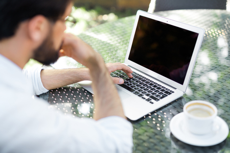 his shirt sleeves: Bearded financial manager with rolled up shirt sleeves searching mistake in his calculations on laptop while drinking coffee in outdoor cafe, over shoulder view
