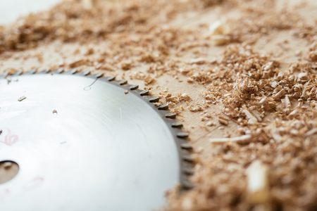 Metal blade of circular saw lying on wooden table with shavings, close-up shot