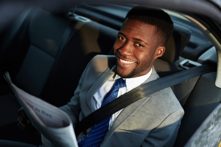 Smiling African Businessman Reading Newspaper in Car
