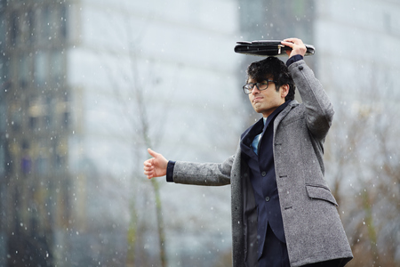 hailing: Businessman Waiting for Taxi in Snow