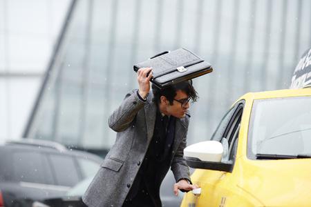 嵐の中のビジネスマンを引くタクシー