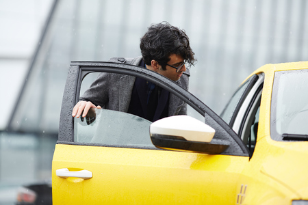 Young Businessman Getting In Taxi Stock Photo
