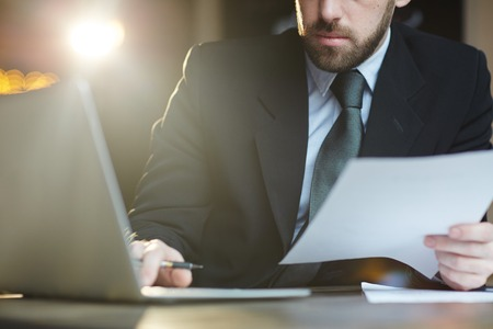 revisando documentos: Hombre de negocios barbudo trabajando con documentos en la Oficina