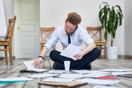 mess: Businessman Sitting on Floor in Office Working