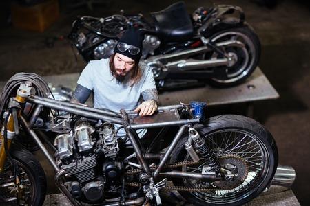 Motocyclette tatouée assemblant moto dans le garage Banque d'images - 76766500