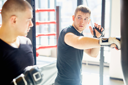 punched out: Two Boxers Practicing Punching Techniques in Sports Club Stock Photo