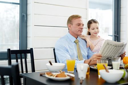 Reading Newspaper at Breakfast Stock Photo - 77507343
