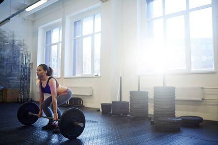 Woman Lifting Heavy Barbell Stock Photo