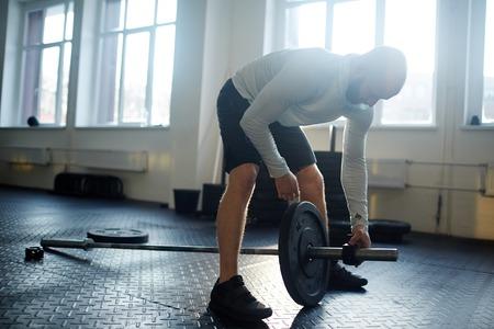 Strong Man Assembling Heavy Barbell