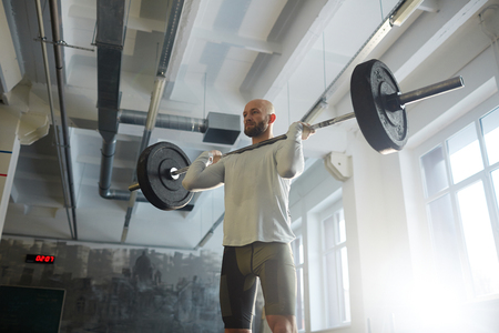 Modern Powerlifter Lifting Barbell in Gym
