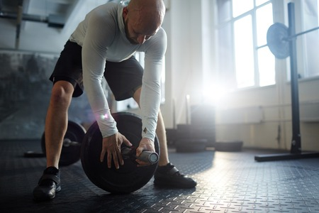 Man Preparing Barbell for Powerlifting Exercise