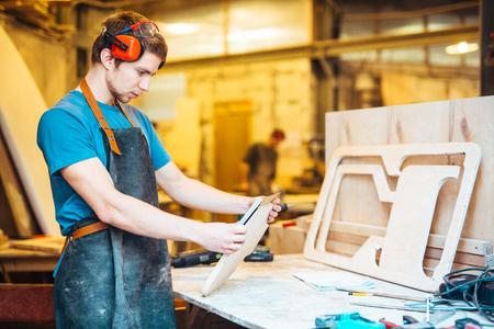 Carpenting ショップで男作る木製家具 写真素材