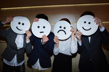 hidden success: Office Workers Trying on Smiling and Sad Masks Stock Photo