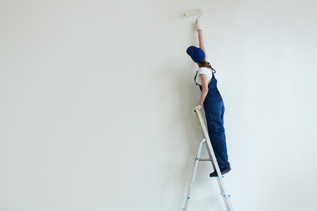 Woman Painting Wall on Stepladder