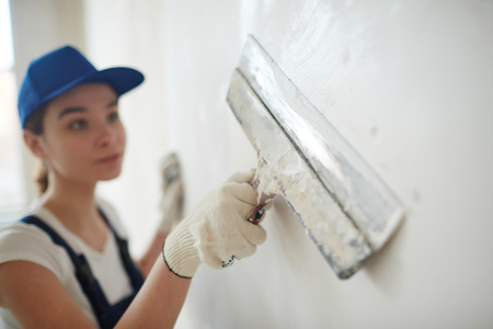 Female Worker Smoothing Out Walls Stock Photo