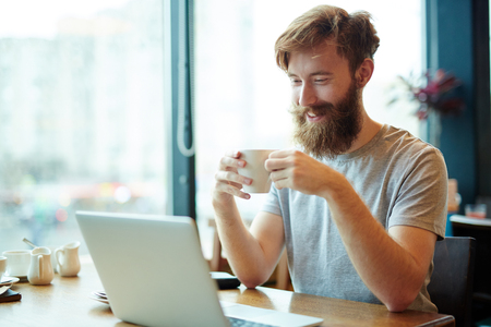 Handsome Businessman Using Laptop in Cafe