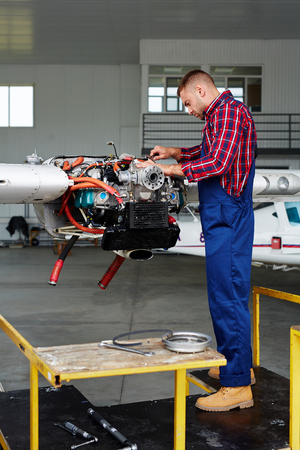 Airplane Engineer Fixing Turbine Stock Photo - 77574106