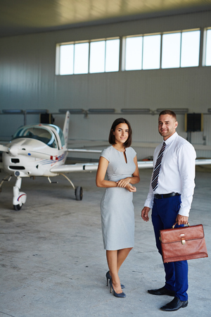 Smiling Business Couple in Airport Hangar Stock Photo