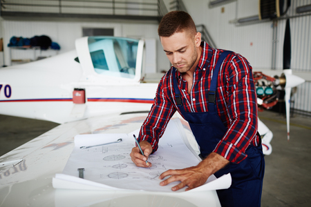 Aircraft Mechanic Working with Plans