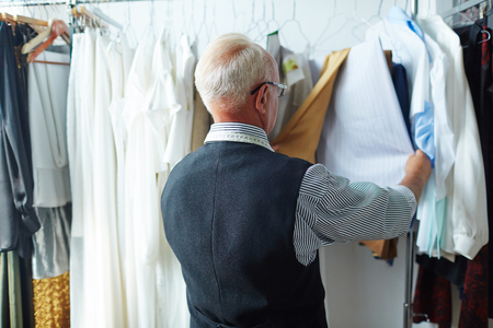 Old Fashioned Artisan Looking at Garments in Tailoring Studio Stock Photo