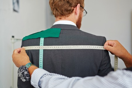 Tailor Taking Measurements on Customer
