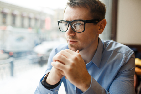 Pensive Businessman in Big Glasses Looking Out Window Banco de Imagens