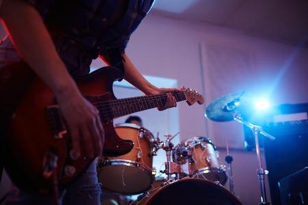 認識できないミュージシャンのギグは、薄暗い照明でギターの弦に焦点を当てる中都市クラブのステージでギターを弾くの中間セクションの肖像画