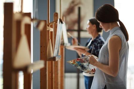 Jonge vrouw kleuren mengen op palet tijdens het schilderen in de kunst klasse