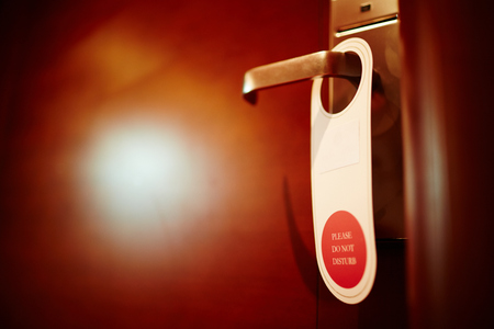 adultery: Closeup shot of do not disturb sign hanging on doorknob of hotel room