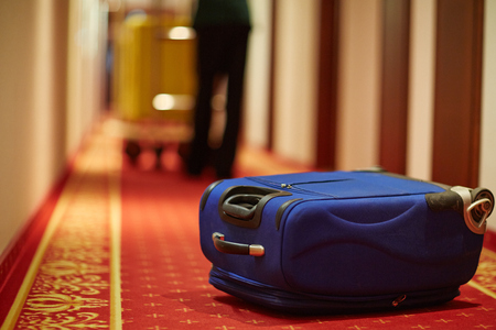 Closeup shot of bellboy carrying luggage in hotel hallway, focus on blue suitcase on floor by room door Stock Photo