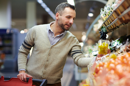 成人男性のスーパー マーケットで食料品を買い