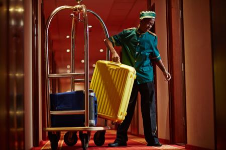 African Bellboy Delivering Luggage to Hotel Rooms Foto de archivo