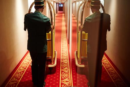 hotel staff: Bellboy Pushing Luggage Cart in Hotel Hallway