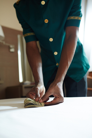 Closeup shot of unrecognizable African bellhop taking cash money from table in hotel room