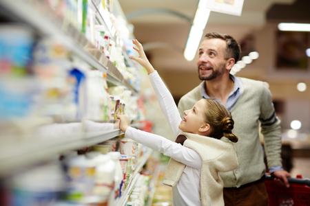 식료품 점에있는 행복한 가족 선택 낙농 제품