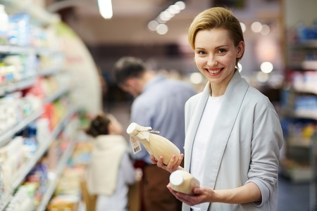super market: Smiling Woman Buying Milk Products Stock Photo