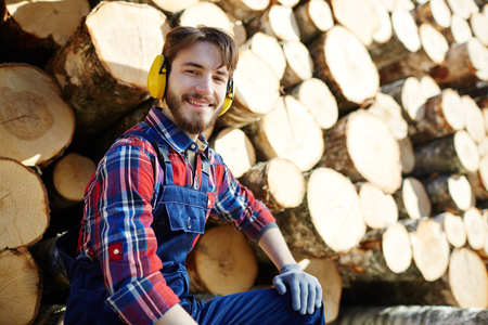 Smiling Lumberjack with Pile of Tree Trunks
