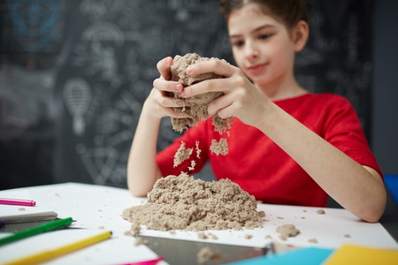 Smiling Girl Playing with Sand in School