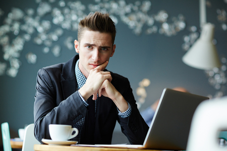 ambitious: Modern Young Businessman Working during Coffee Break Stock Photo