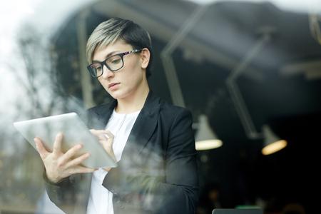 Empresaria moderna que trabaja con el dispositivo de la tableta Foto de archivo - 78545677