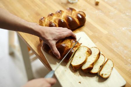 Cutting fresh bread Фото со стока