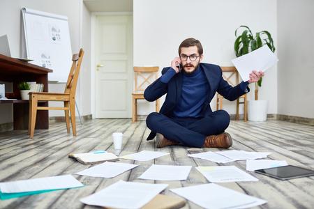 Agitated Businessman Working on Floor in Office Reklamní fotografie