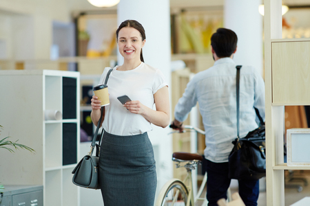 Smiling Young Woman Leaving Modern Office Stock Photo