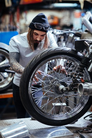 Tattooed Mechanic Assembling Motorcycle in Workshop Garage Stock Photo
